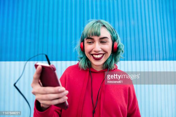 portrait of laughing young woman with blue dyed hair with headphones taking selfie with smartphone - hoodie headphones stock pictures, royalty-free photos & images
