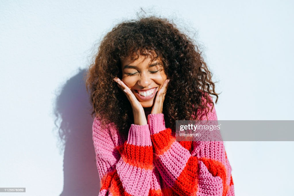 Portrait of laughing young woman with curly hair against white wall : Foto de stock