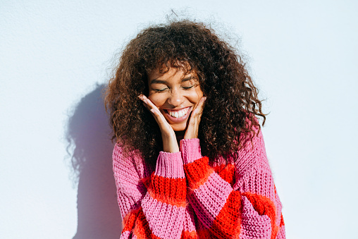 Portrait of laughing young woman with curly hair against white wall - gettyimageskorea