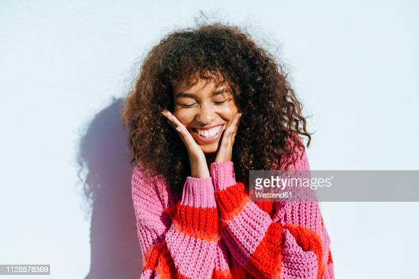portrait of laughing young woman with curly hair against white wall - lachen stock-fotos und bilder