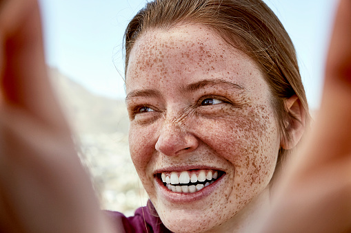 Portrait of laughing young woman with freckles outdoors - gettyimageskorea