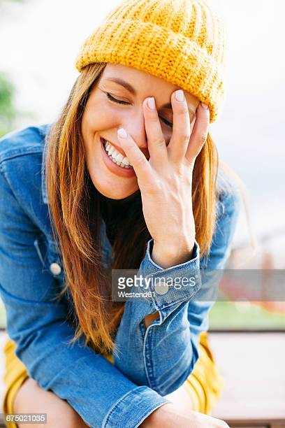 portrait of laughing young woman with hand on her face - mütze stock-fotos und bilder