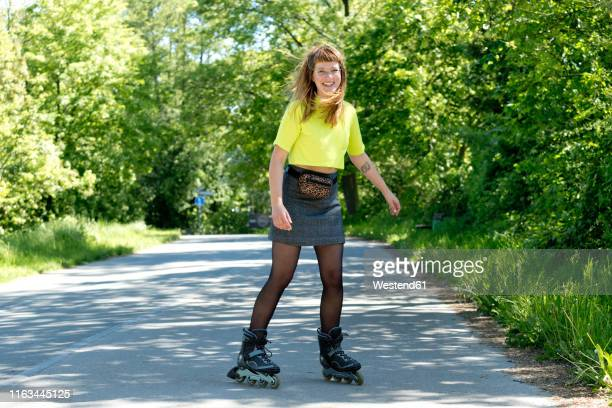 portrait of laughing young woman with inline skates - ウエストポーチ ストックフォトと画像