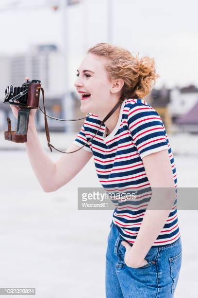 portrait of laughing young woman with vintage camera - desaturated stock pictures, royalty-free photos & images