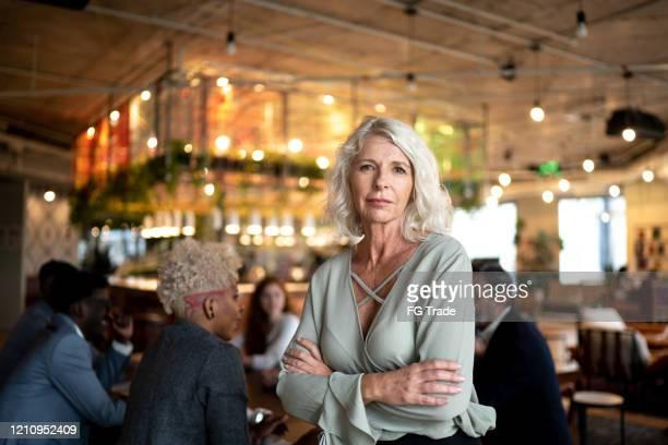 portrait of leader mature businesswoman at conference table - fundador imagens e fotografias de stock