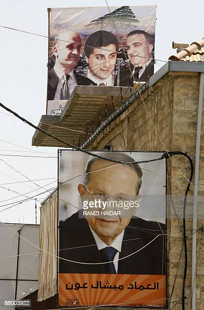 A portrait of Lebanese Christian opposition leader Michel Aoun hangs under a poster of Tourism Minister Elie Marouni Lebanese Forces party leader...