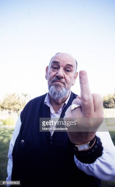 Portrait of Led Zeppelin manager Peter Grant raising his middle finger at home in Eastbourne United Kingdom 1993