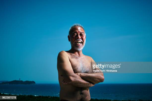 portrait of legendary surfer at the roof of his house - old nudists stock pictures, royalty-free photos & images