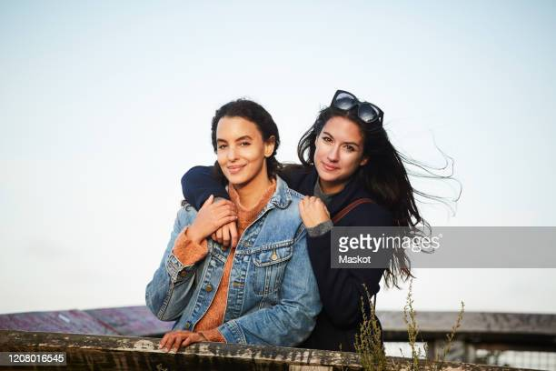 portrait of lesbian couple standing at observation point against sky - lesbian stock pictures, royalty-free photos & images