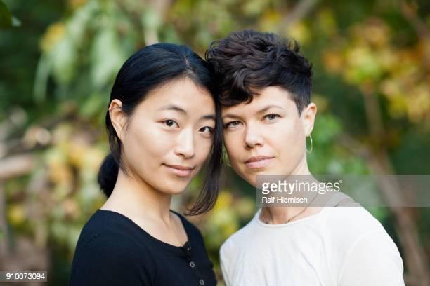 Portrait of lesbian couple standing at park