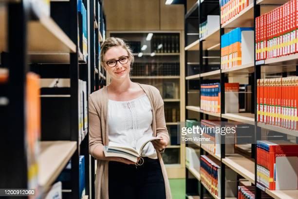 portrait of librarian leaning on bookshelf in library - literatur stock-fotos und bilder