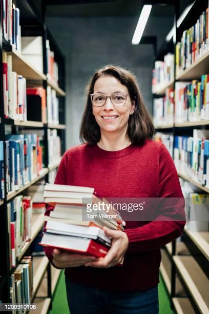 portrait of librarian organizing books in public library - bibliothekar stock-fotos und bilder