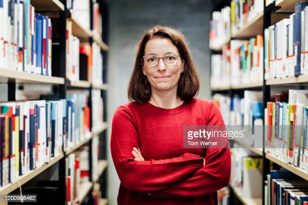 portrait of librarian with arms crossed - focus on foreground stock pictures, royalty-free photos & images