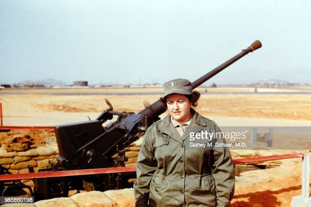 Portrait of Lieutenant Jean Schihman of the 8063rd MASH as she stands beside an antiaircraft gun at Kimpo Air Base Seoul South Korea April 1952