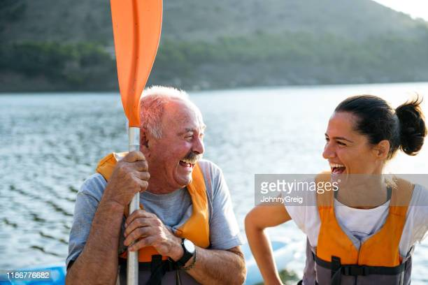 portrait of lighthearted senior kayaker and paddling friend - southern european descent stock pictures, royalty-free photos & images