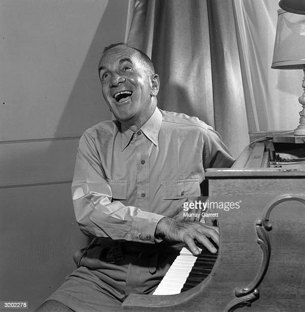 Portrait of Lithuanianborn singer and actor Al Jolson singing and playing the piano while sitting sideways at the keyboard in his home Beverly Hills...