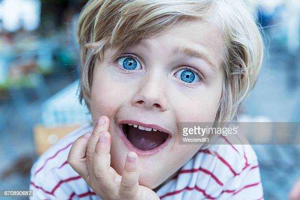 portrait of little blond boy with eyes wide open and open mouth - menino loiro olhos azuis imagens e fotografias de stock