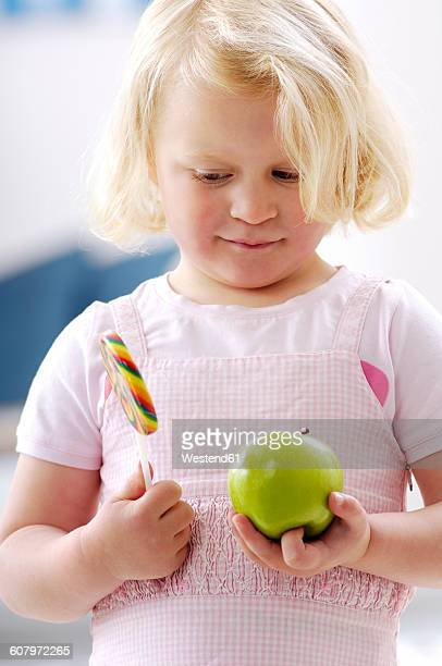 Portrait of little blond girl holding a green apple and a lollipop
