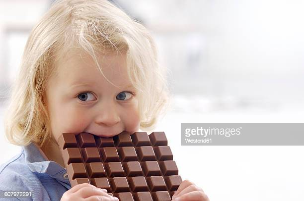 Portrait of little blond girl with chocolate bar