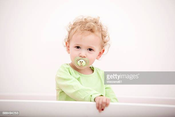 Portrait of little blond girl with pacifier standing in cot