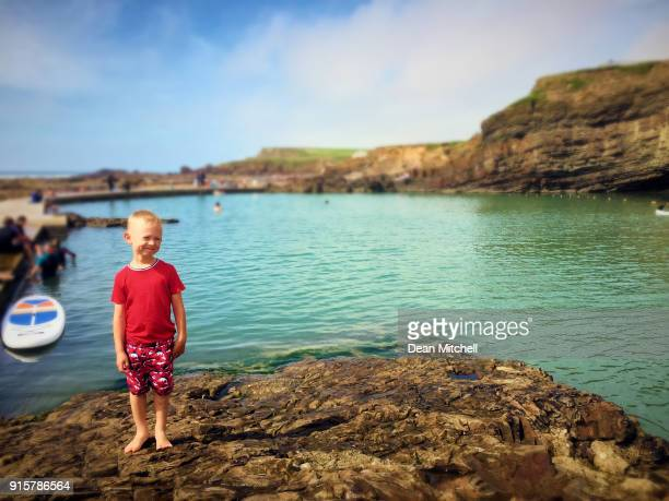 portrait of little boy by natural sea pool cornwall - taken on mobile device stock photos and pictures