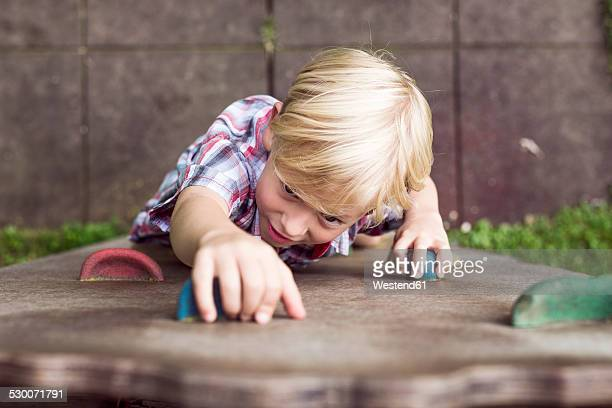 Portrait of little boy climbing on a playground