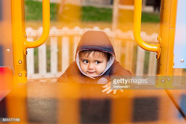 portrait of little boy climbing on playground equipment - hood clothing stock photos and pictures