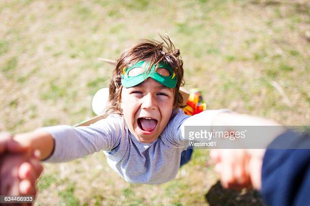 Portrait of little boy dressed up as a superhero playing with his father on a meadow