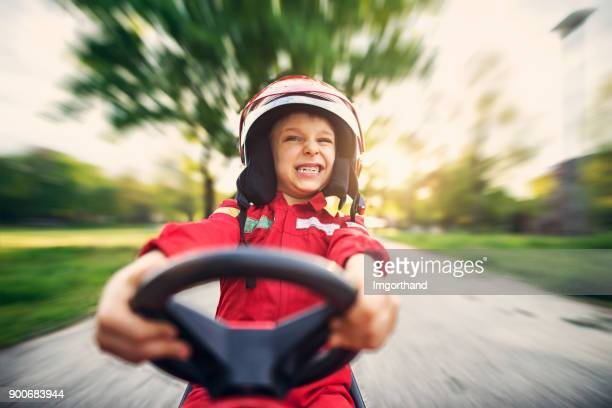portrait of little boy driving fast his toy car - motorsport stock pictures, royalty-free photos & images