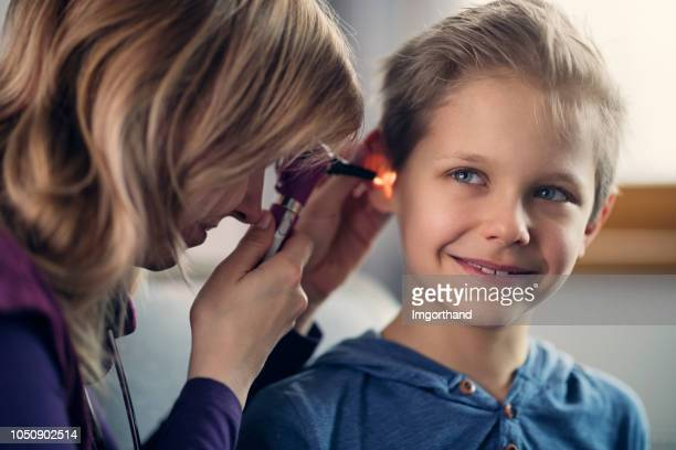 portrait of little boy having an ear examination - ear exam stock photos and pictures