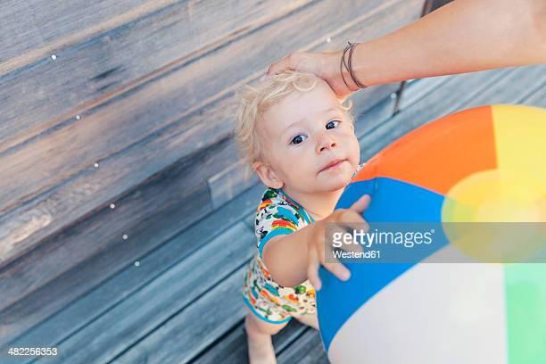 Portrait of little boy holding beach ball