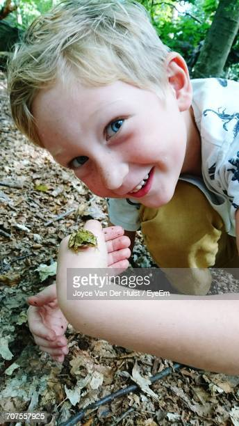 Portrait Of Little Boy Holding Small Frog In Forest