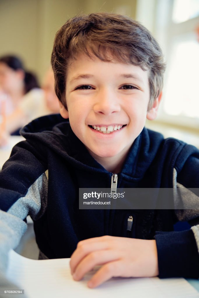 Portrait of little boy in classroom, sitting at his desk. : Stock Photo