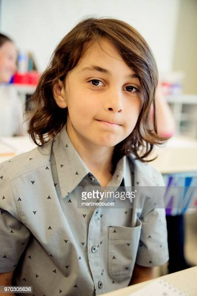 Portrait of little boy in classroom, sitting at his desk.