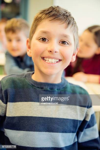 """portrait of little boy in classroom, sitting at his desk. - """"martine doucet"""" or martinedoucet stock pictures, royalty-free photos & images"""