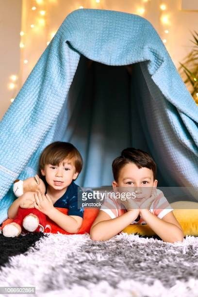portrait of little boy in front of tent with brother - fort stock pictures, royalty-free photos & images