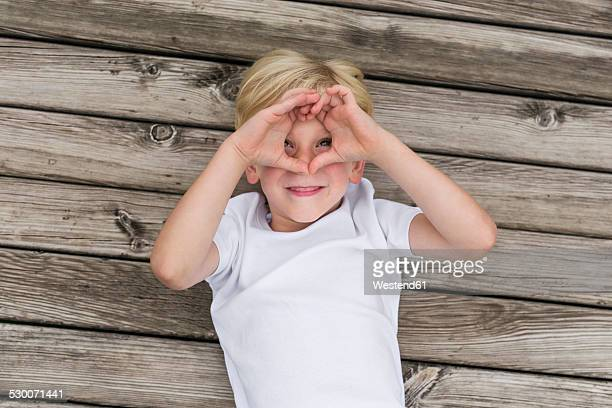 Portrait of little boy lying on a jetty shielding his eyes with his hands