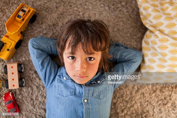 Portrait of little boy lying on carpet with toy cars besides him