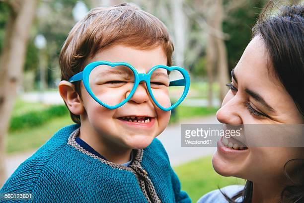 Portrait of little boy making faces with heart shaped glasses