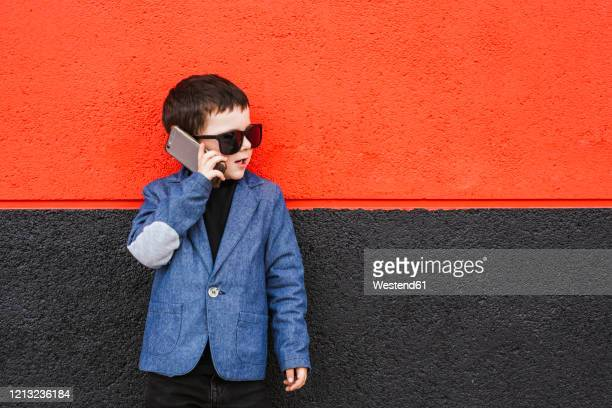 portrait of little boy on the phone wearing suit coat and oversized sunglasses - adult imitation stock pictures, royalty-free photos & images