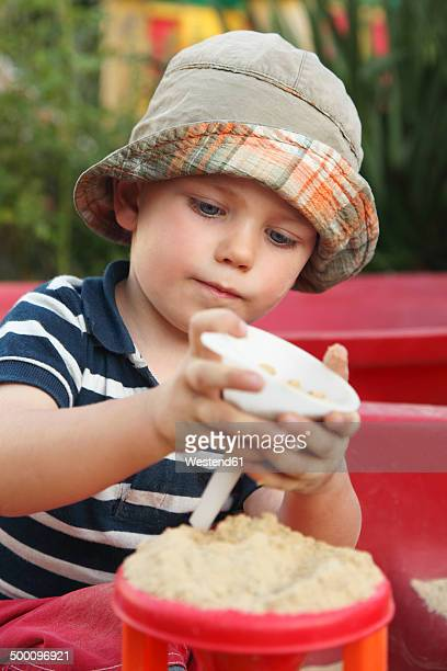 Portrait of little boy playing in sand box