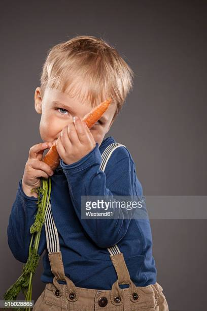 Portrait of little boy playing with a carrot