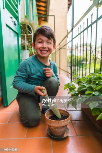 portrait of little boy pulling funny face on balcony - jardinier humour photos et images de collection