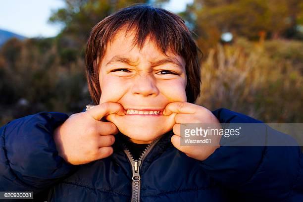 Portrait of little boy pulling funny faces