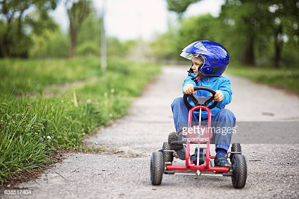 portrait of little boy riding a go-kart. - spring racing stock photos and pictures