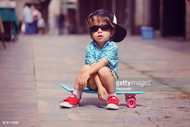 Portrait of little boy sitting on skateboard wearing oversized sunglasses and basecap