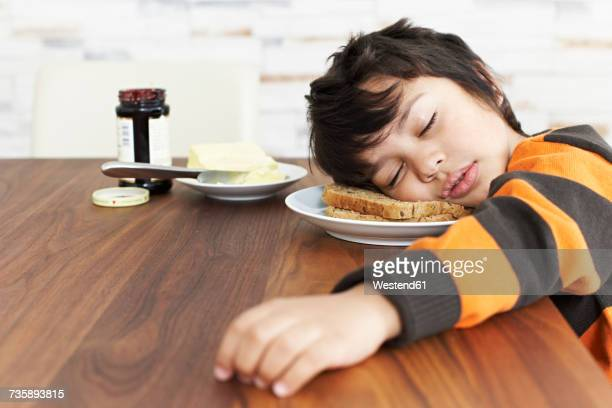 portrait of little boy sleeping at breakfast table - dormir humour photos et images de collection