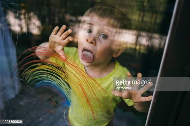 portrait of little boy standing behind balcony door licking glass pane with drawn rainbow - likken stockfoto's en -beelden