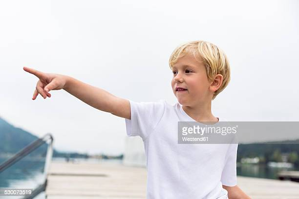 portrait of little boy standing on a jetty pointing on something - menschlicher finger stock-fotos und bilder