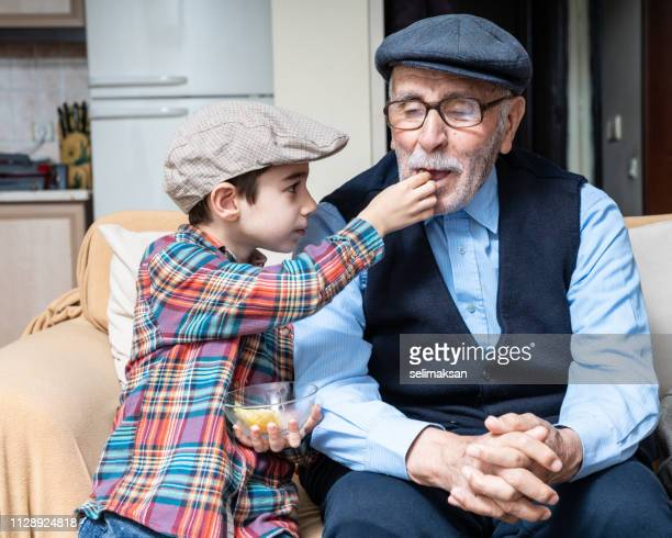 Portrait of Little Boy Taking Care Of His Great Grandfather